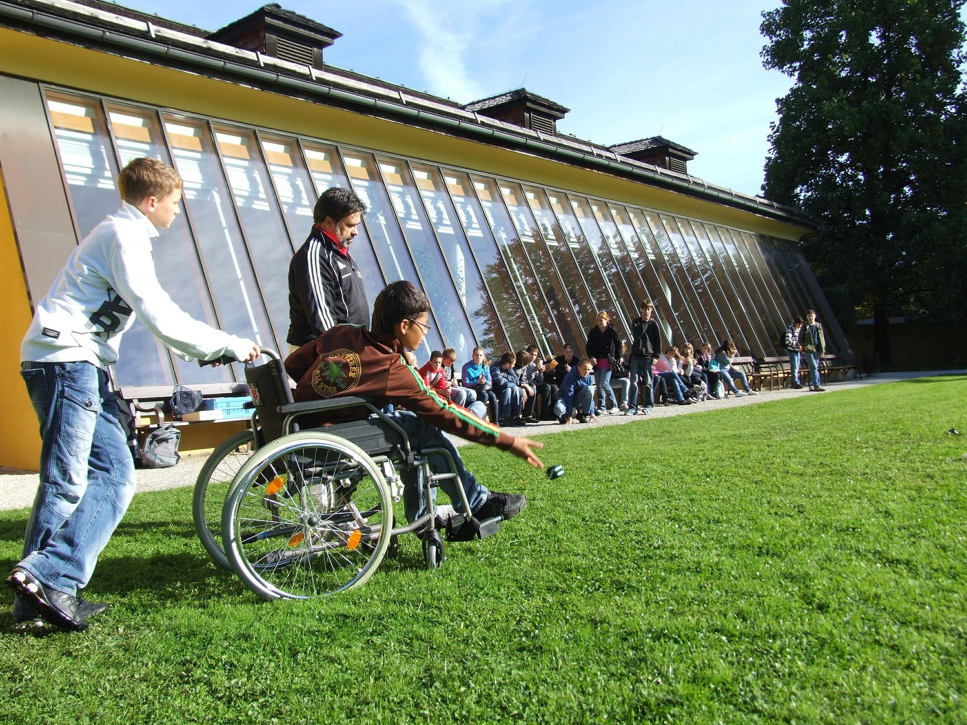 Kind speelt jeu de boule in rolstoel